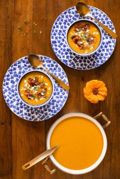 Overhead vertical photo of a pot and serving bowls of Roasted Butternut Squash Soup with Crispy Pancetta on a wood table.