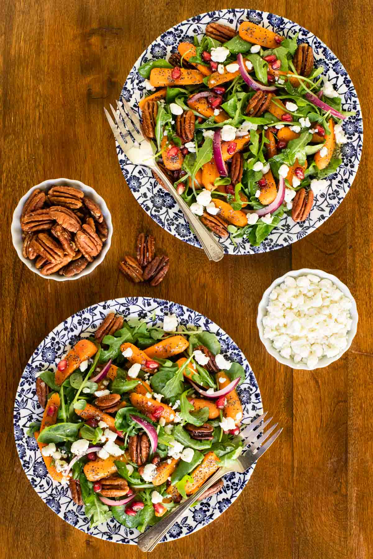 Overhead vertical photo of two individual servings of Roasted Carrot Salad with Cider Poppy Seed Dressing on blue and white patterned plates.