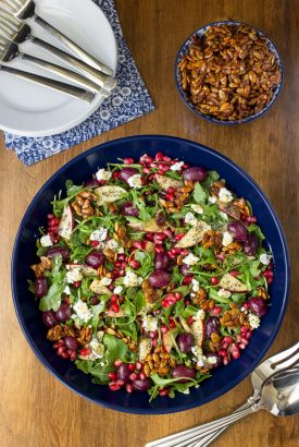 Overhead picture of Roasted Grape Arugula Salad in a blue bowl on a wooden table