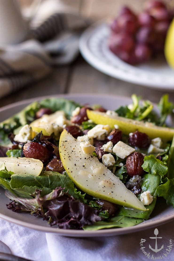 15 Delicious Fall Recipes - Photo of a plate of Roasted Grape Salad with Pears, Blue Cheese and Maple Dressing on a wood table with a plate of fruit in the background.