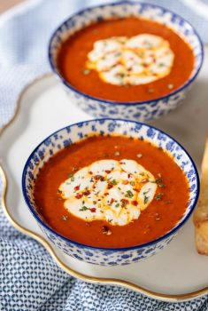 Vertical picture of Roasted Red Pepper Tomato Soup topped with mozzarella in blue and white bowls