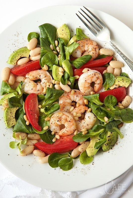 Vertical photo of a plate filled with Roasted Shrimp, Tomato and White Bean Salad.