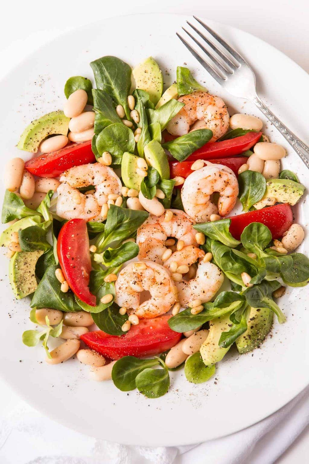 Overhead picture of Roasted Shrimp, Tomato and White Bean Salad on a white plate