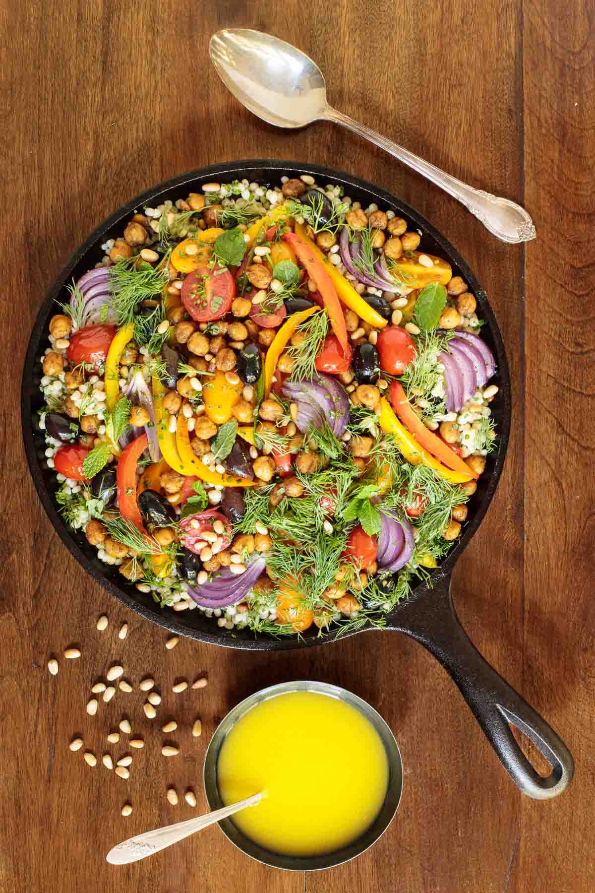 Overhead picture of roasted veggie salad in a cast iron skillet on a wooden table with dressing