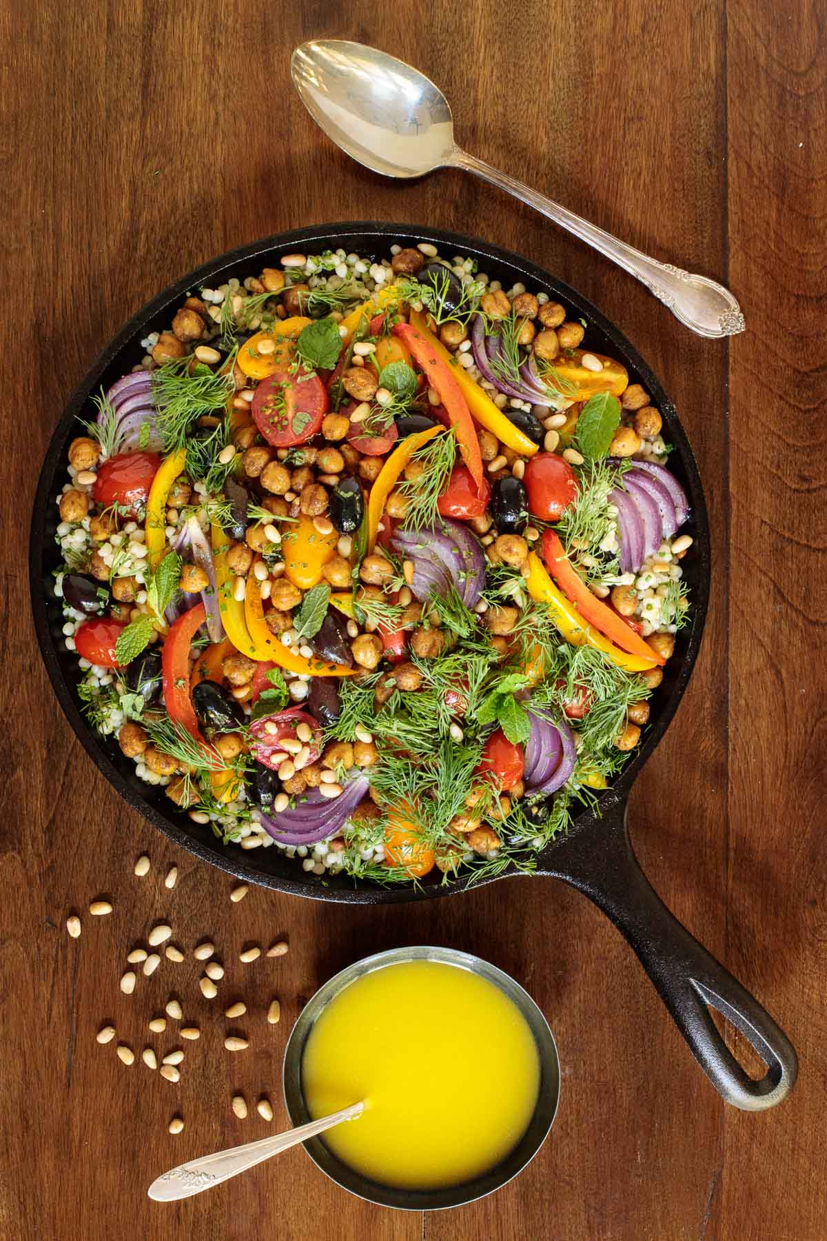 Overhead photo of a black cast iron skillet filled with Roasted Veggie and Crispy Chickpea Salad on a wood table.