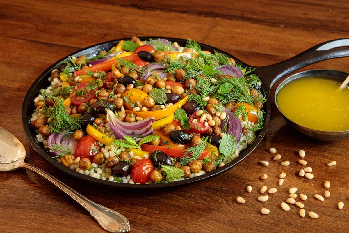Photo of a cast iron skillet filled with Roasted Veggie and Crispy Chickpea Salad on a wood table.