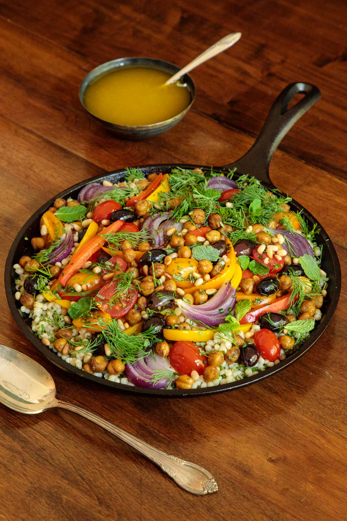 Photo of a cast iron skillet filled with Roasted Veggie and Crispy Chickpea Salad.