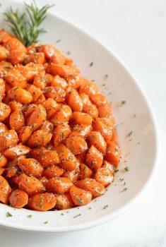 Vertical image of honey glazed carrots on a white platter