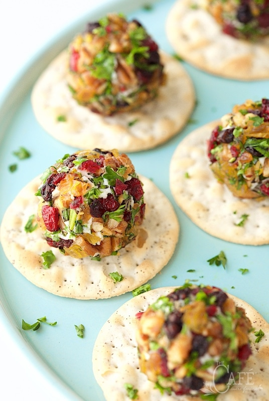 Vertical picture of goat cheese truffles on crackers on a light blue stand