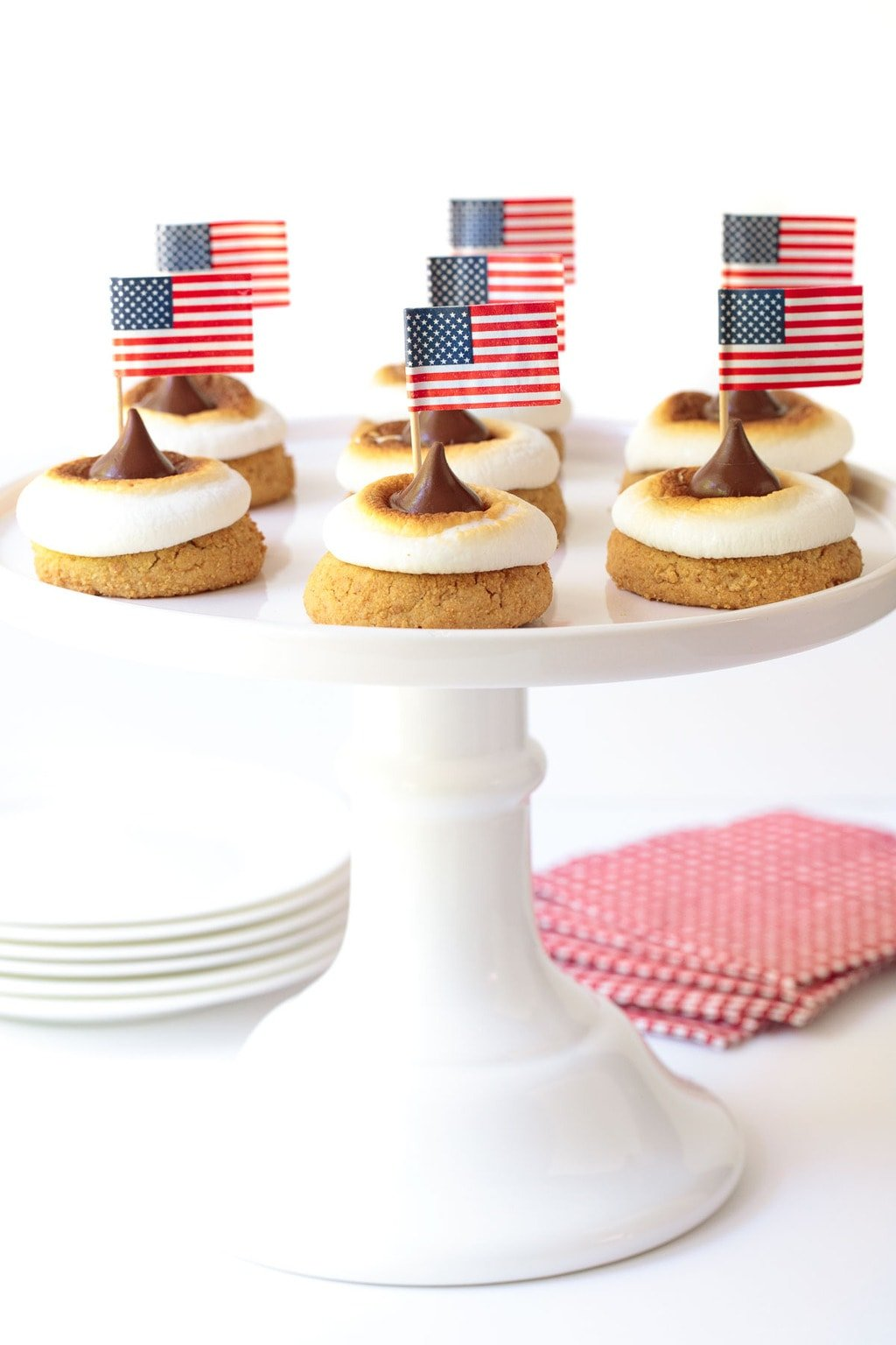 Vertical picture of S'Mores Blossom Cookies topped with American flagson a white cake stand