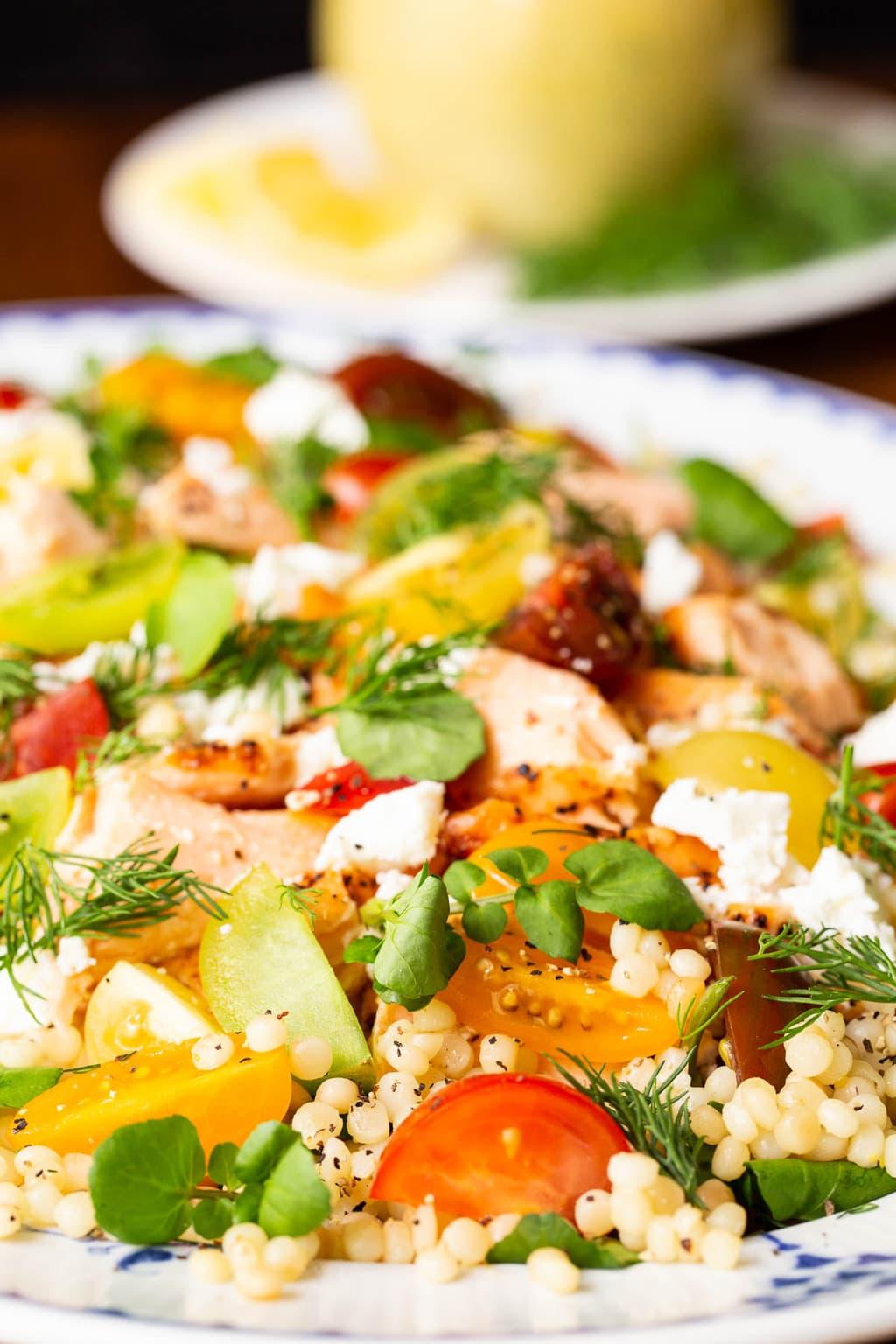 Vertical closeup photo of a presentation platter of Israeli Couscous Salmon Salad.