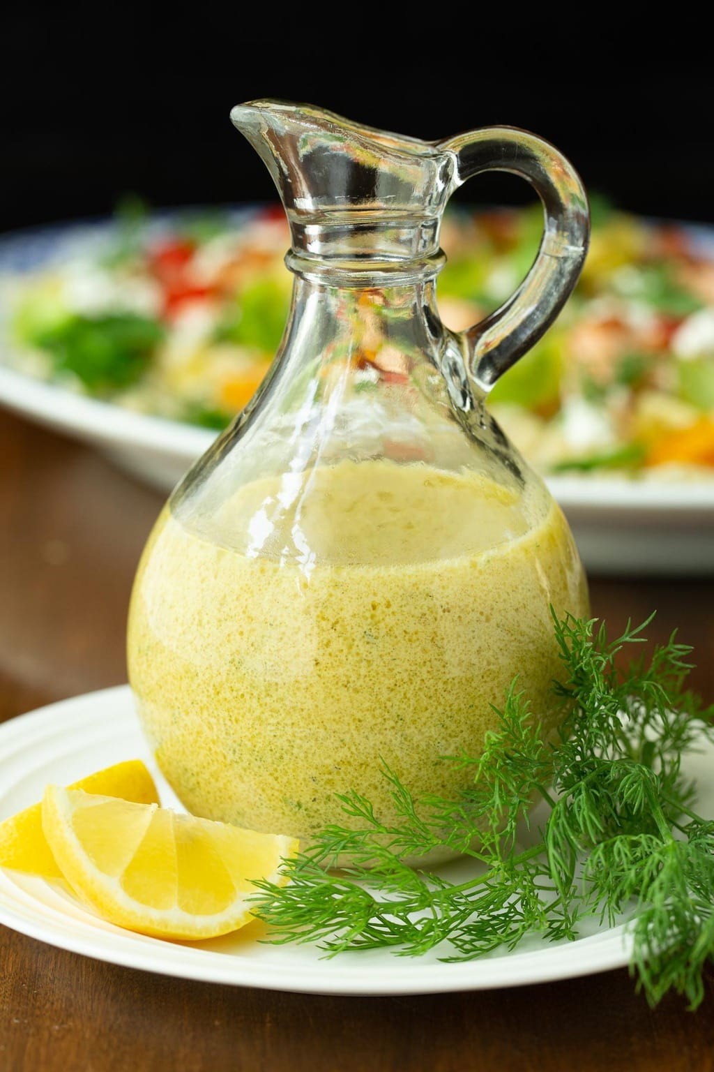 Closeup vertical photo of a glass pitcher of Lemon Dill Dressing with a plate of Israeli Couscous Salmon Salad in the background.