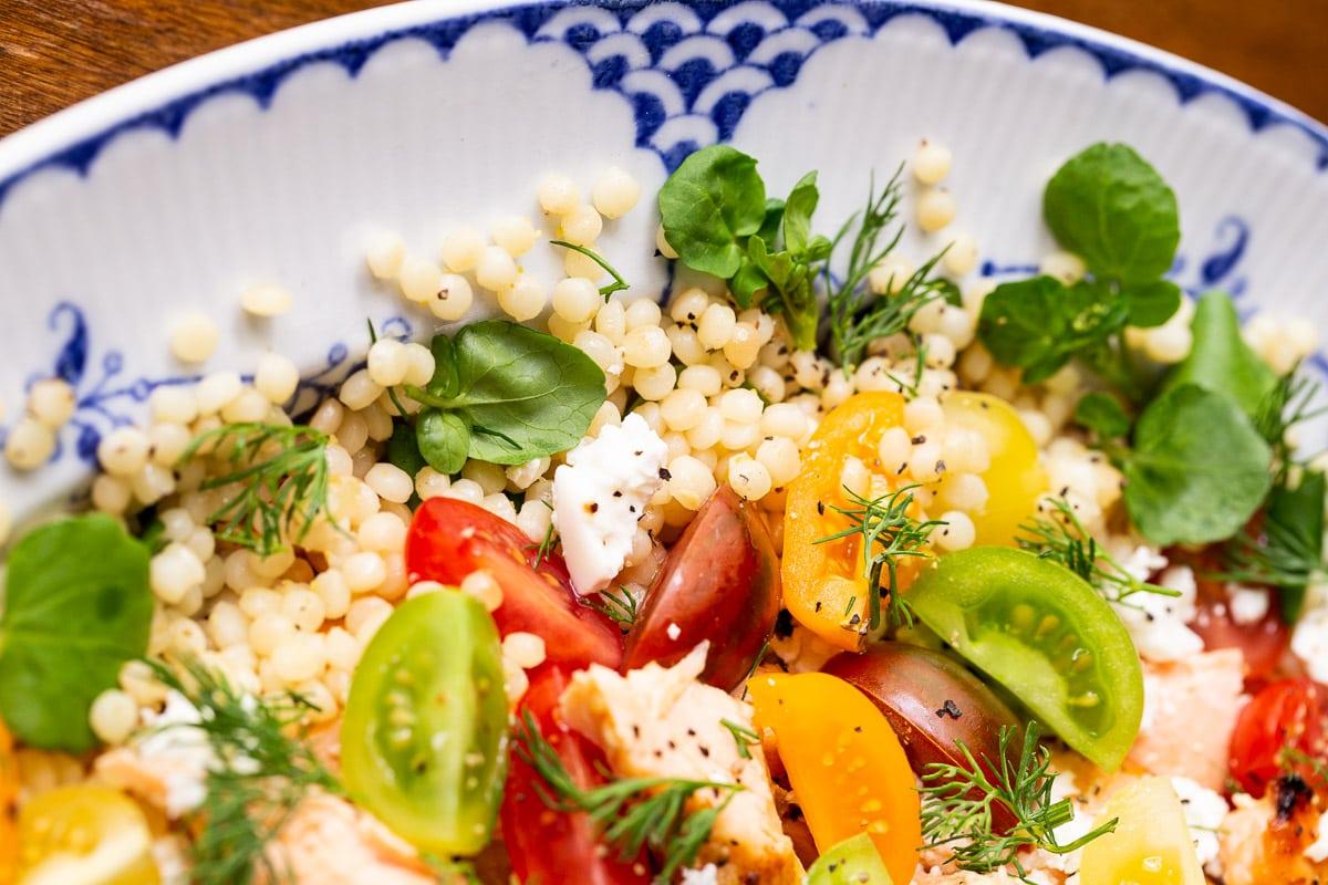 Horizontal extreme closeup photo of a platter of Israeli Couscous Salmon Salad.