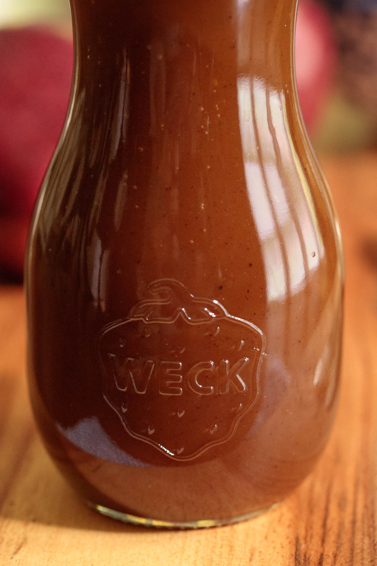 Closeup photo of a glass Weck jar filled with Apple Cider Caramel Sauce on a wood surface.