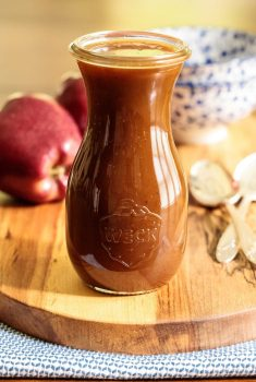Vertical picture of apple cider caramel sauce in a glass jar