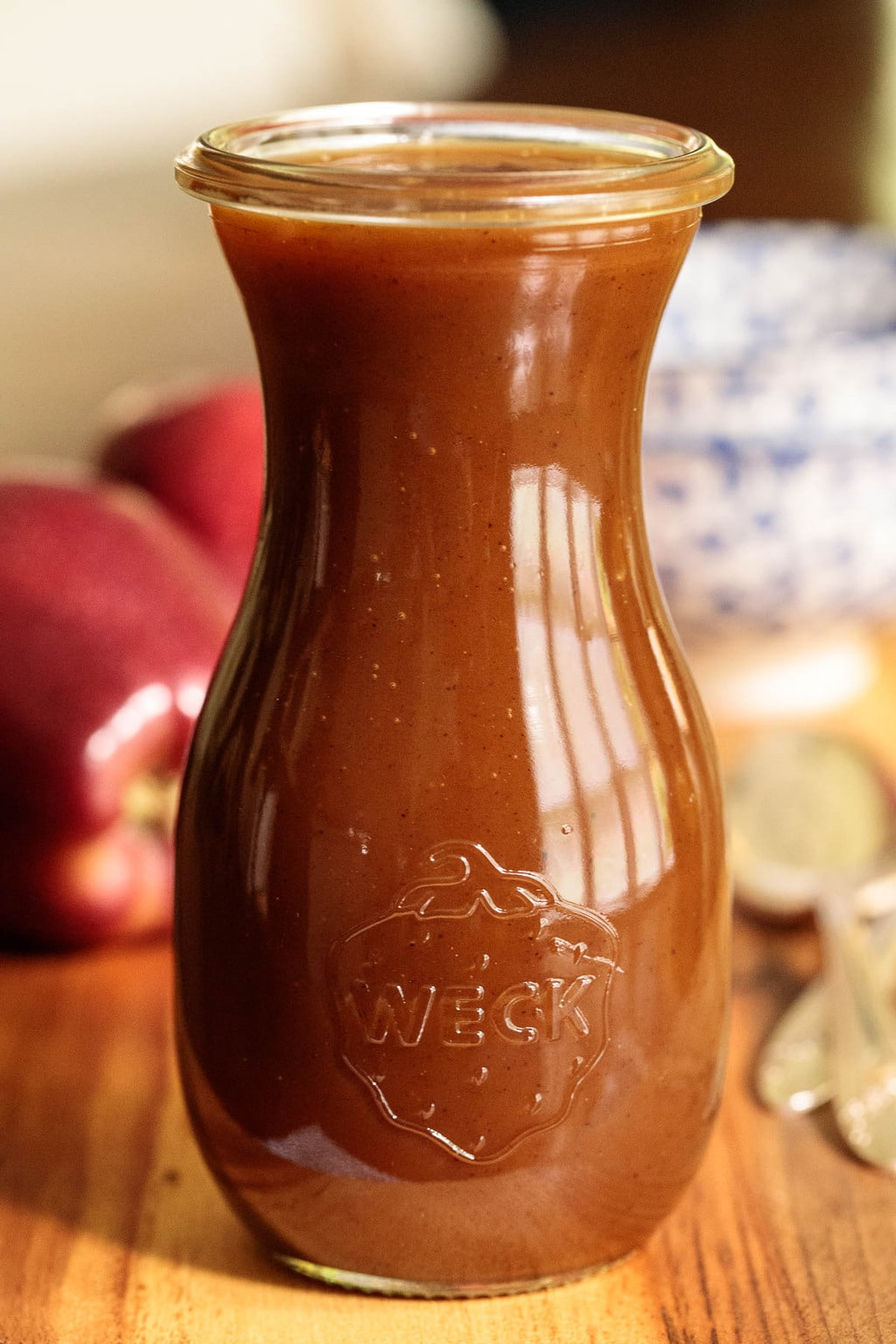 Photo of a Weck jar filled with Salted Apple Caramel Sauce. Fresh red apples are in the the background.