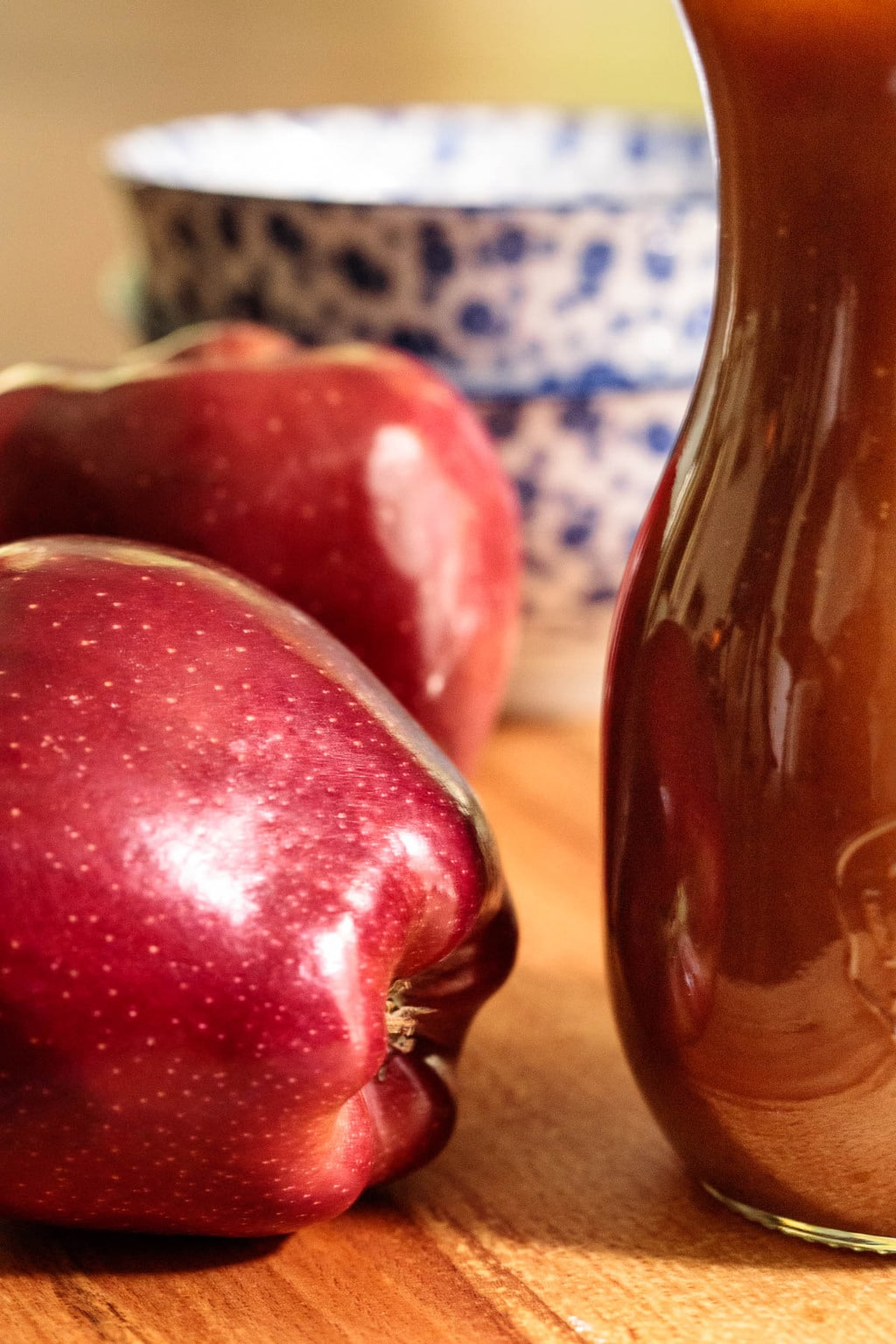 Photo of a glass jar of Salted Apple Cider Caramel Sauce on a wood table with red apples and serving dishes in the foreground and background.