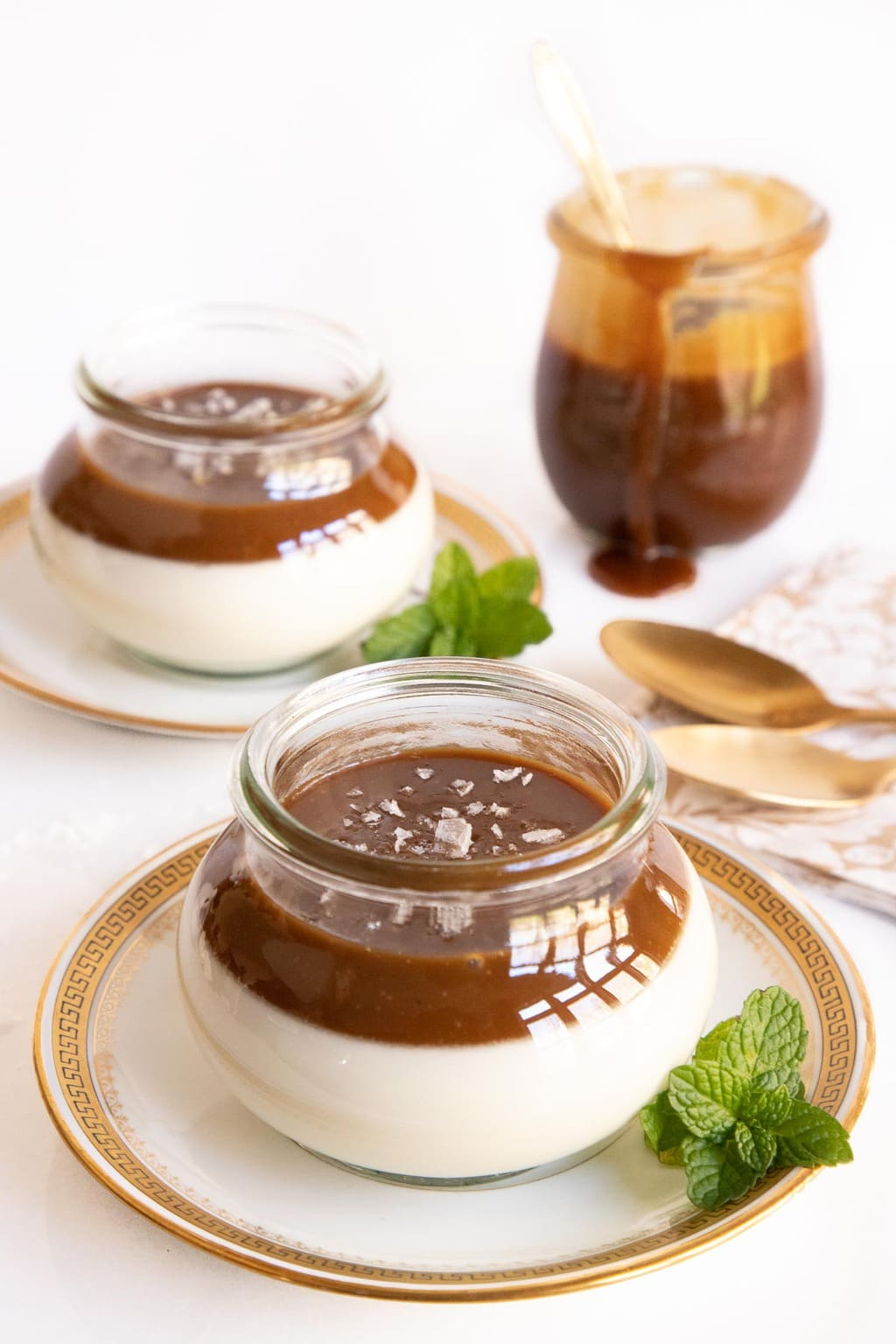 Vertical photo of Salted Butterscotch Panna Cotta in glass Weck jars garnished with fresh mint leaves.