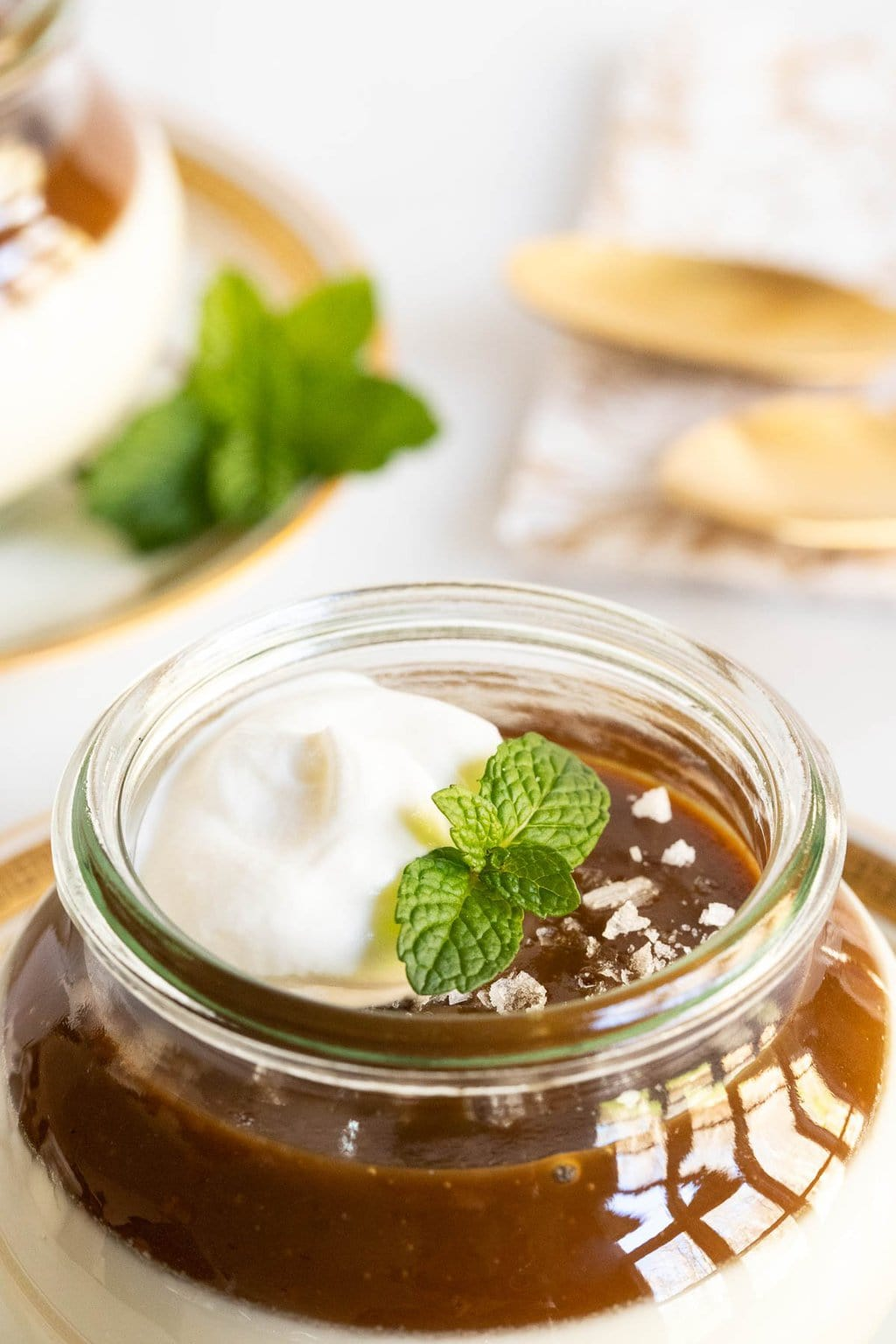 Vertical closeup photo of the top of a jar filled with Salted Butterscotch Panna Cotta and garnished with whipped cream and a sprig of fresh mint.
