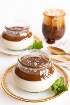 Vertical photo of glass jars filled with Salted Butterscotch Panna Cotta.