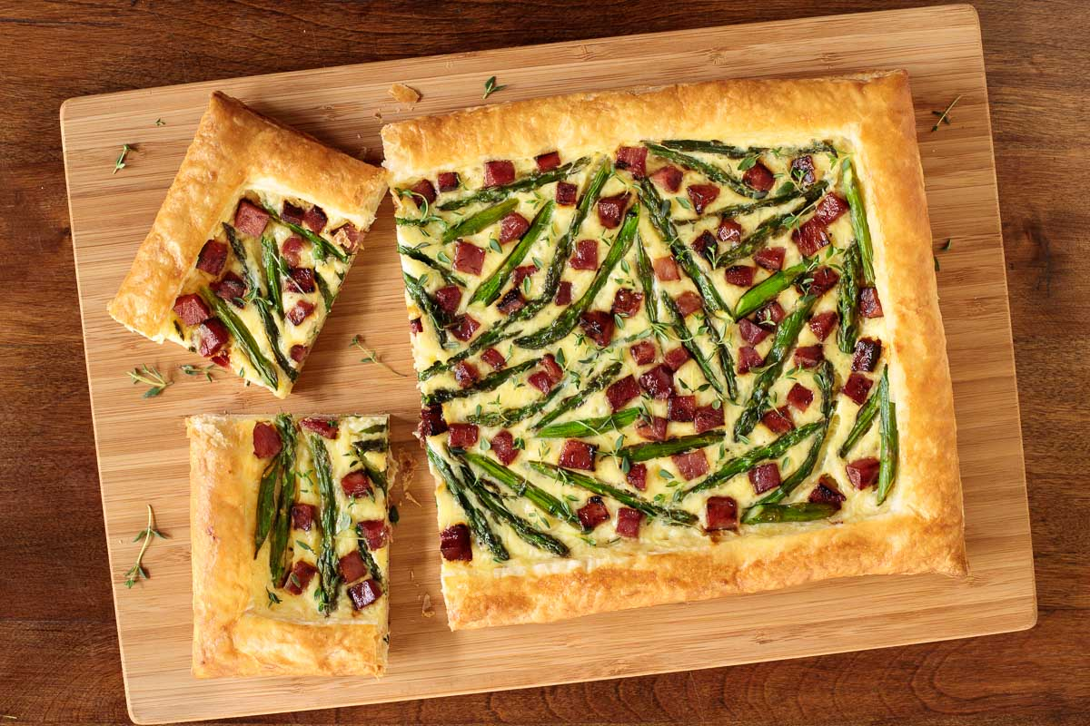Photo of the finished product, a baked Easy Savory Puff Pastry Tart with asparagus and ham.