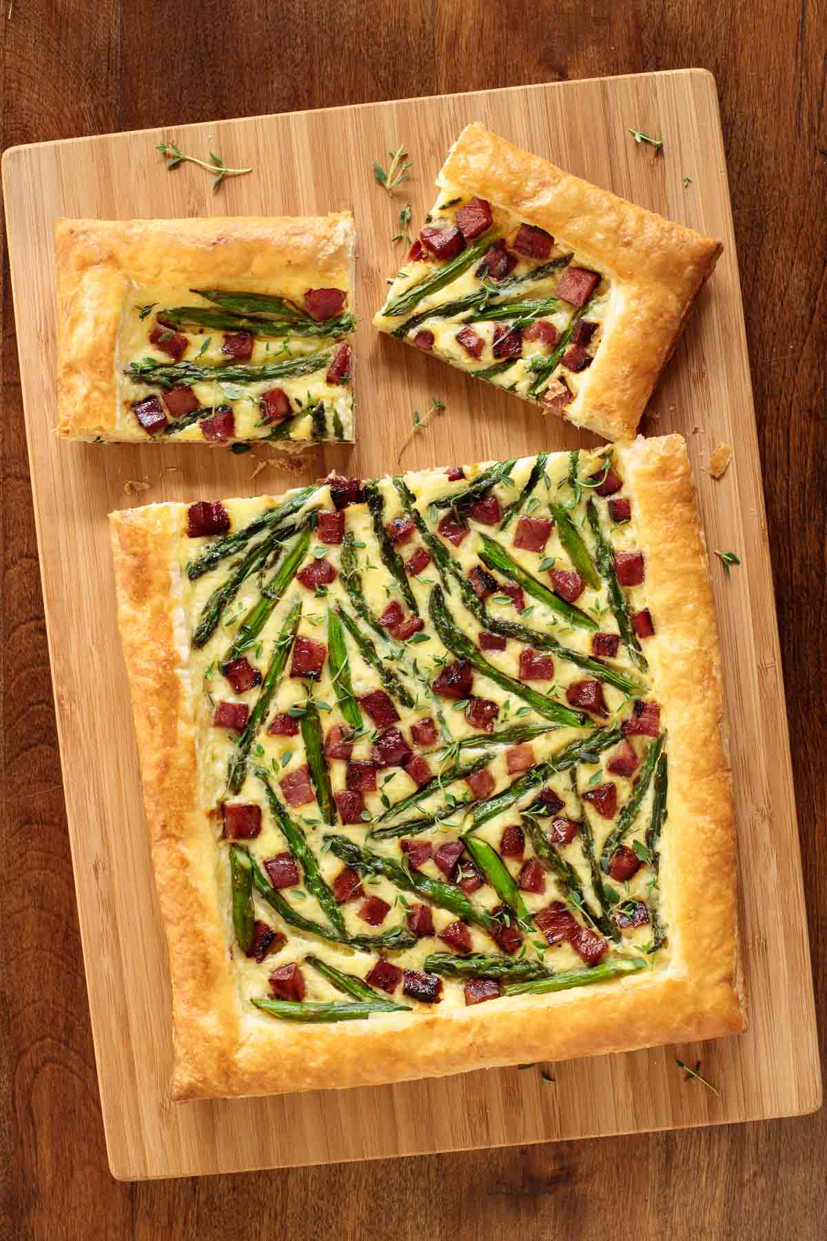 Overhead picture of savory puff pastry tart on a wooden cutting board