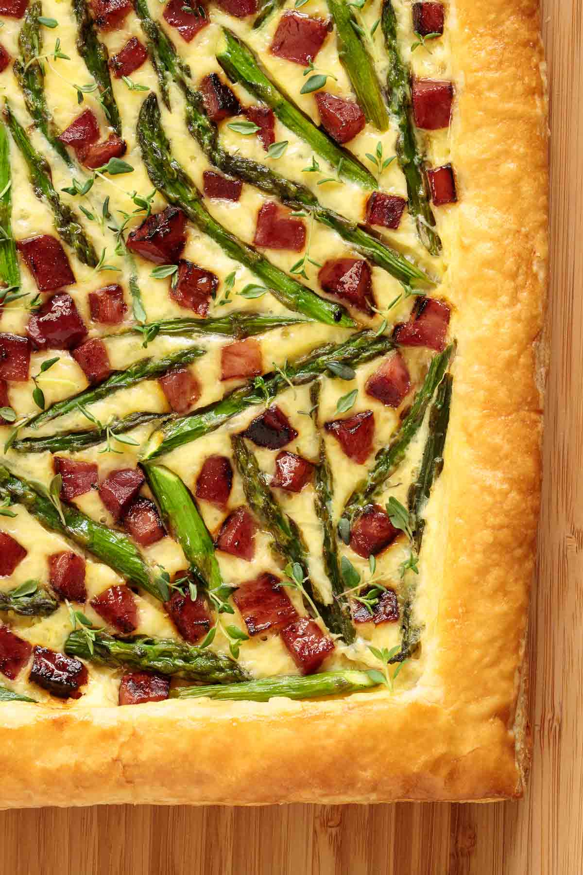 Closeup photo of one side of an Easy Savory Puff Pastry Tart on a bamboo cutting board.
