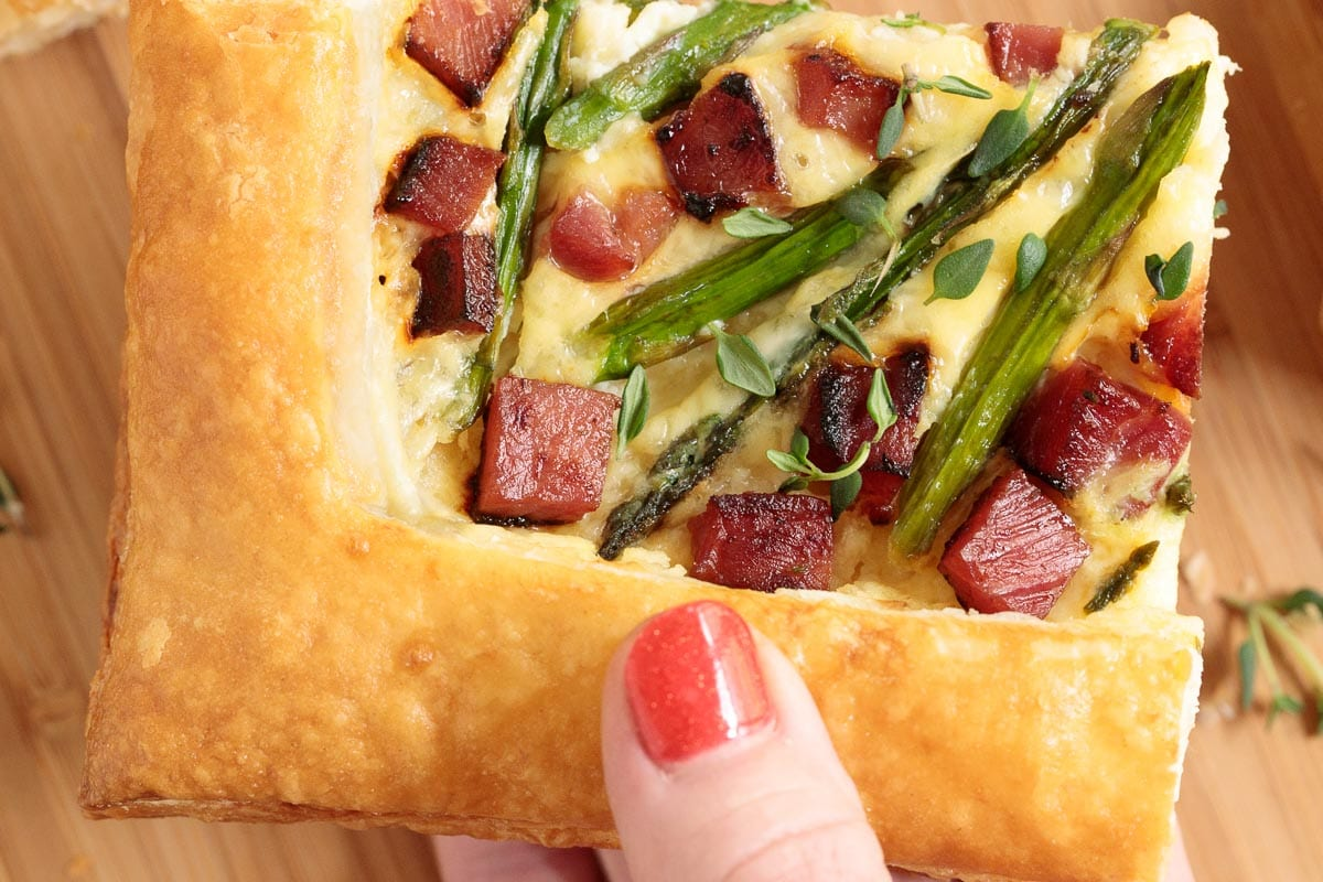 A photo of a person holding up a slice of Easy Savory Puff Pastry Tart.