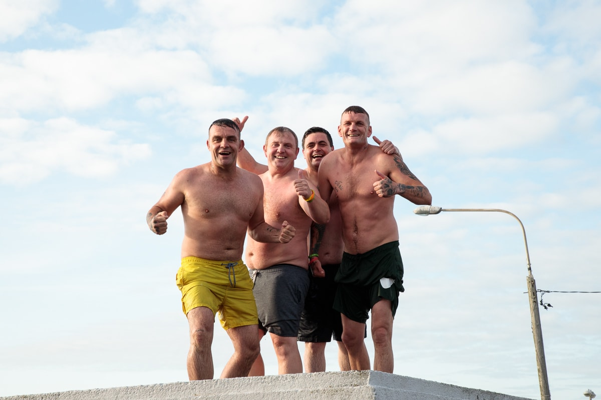 Photo of four guy swimmers who were diving off the top of the dock at Ballycotton, Northern Ireland.