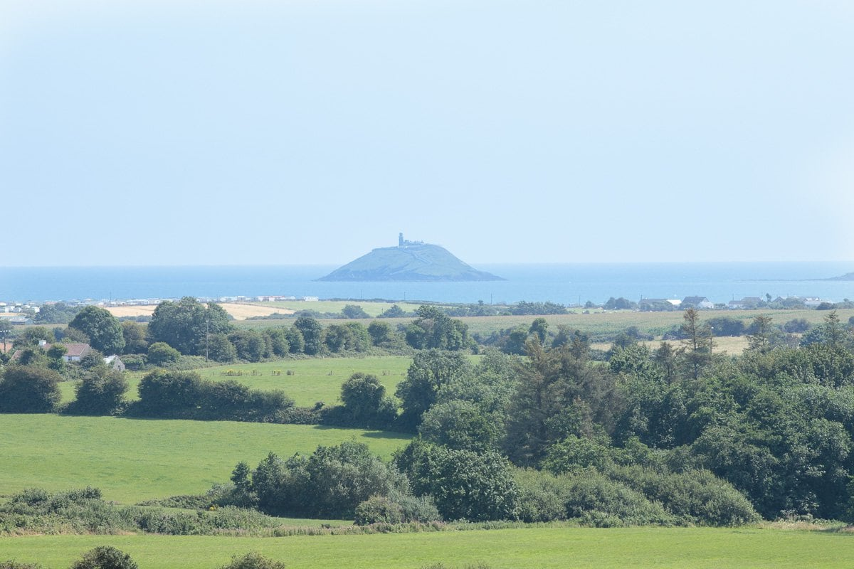 Long view photo of the Ballycotton countryside and lighthouse.