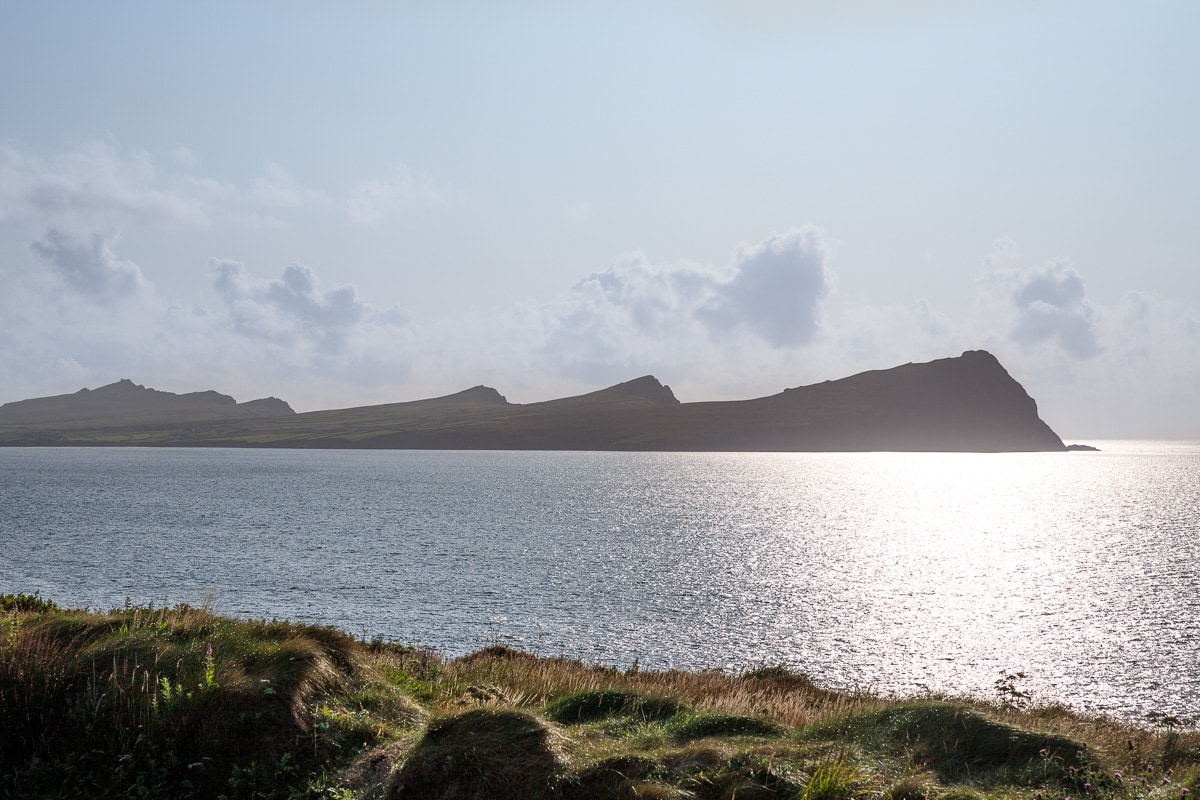 Photo of hills and the ocean reflecting sunlight along the Dingle Peninsula in Ireland.