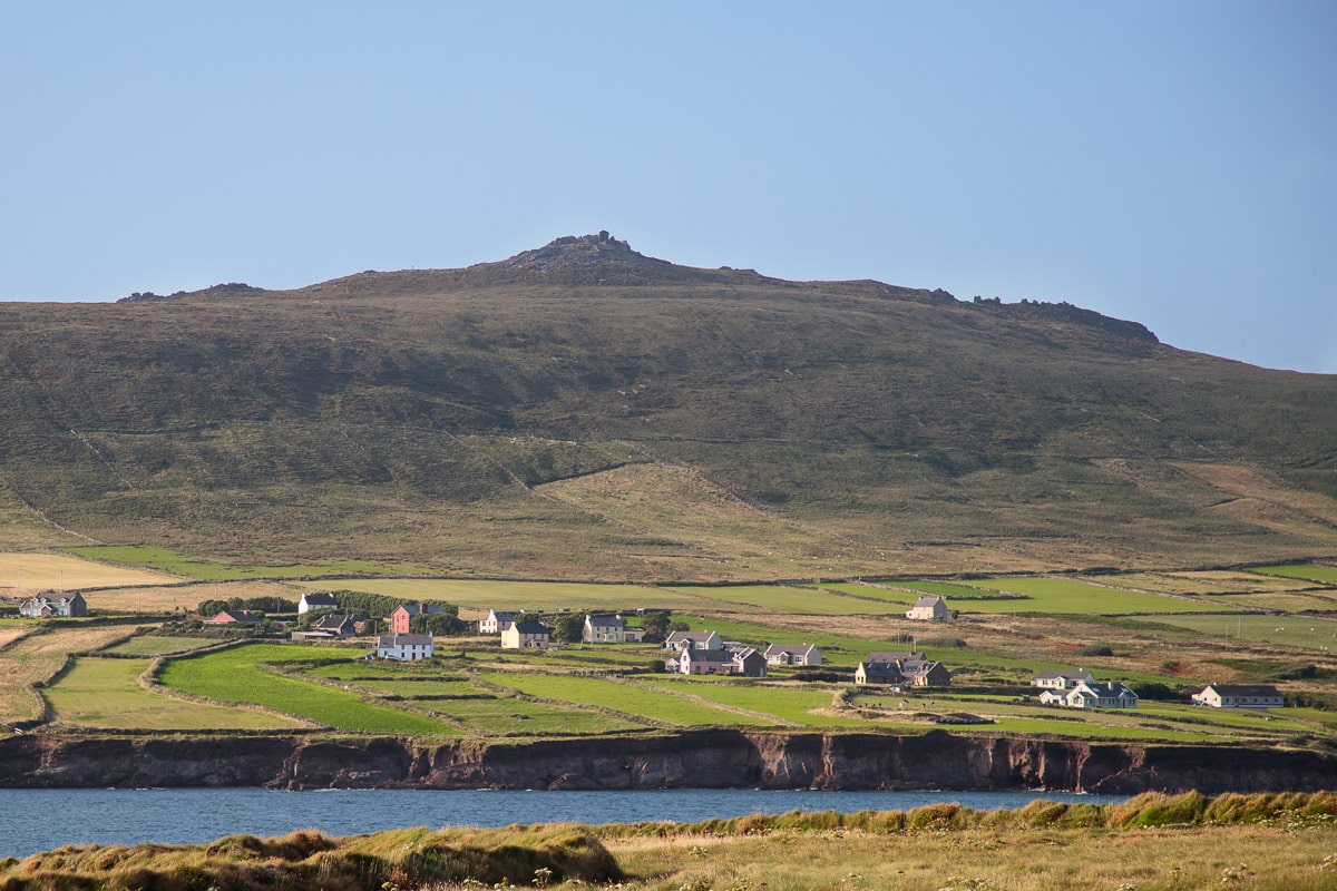 Photo of the hillsides and a small village around the Dingle Peninsula, Ireland.