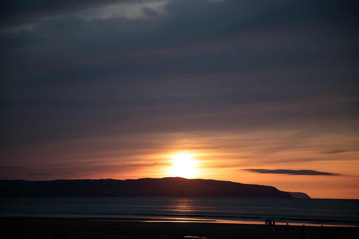Photo of the sun setting on a beach in Portstewart, Northern Ireland.