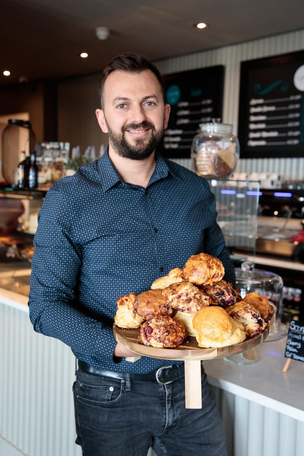 Photo of the very proud manager of Castello Italia restaurant holding a plate of fresh scones.