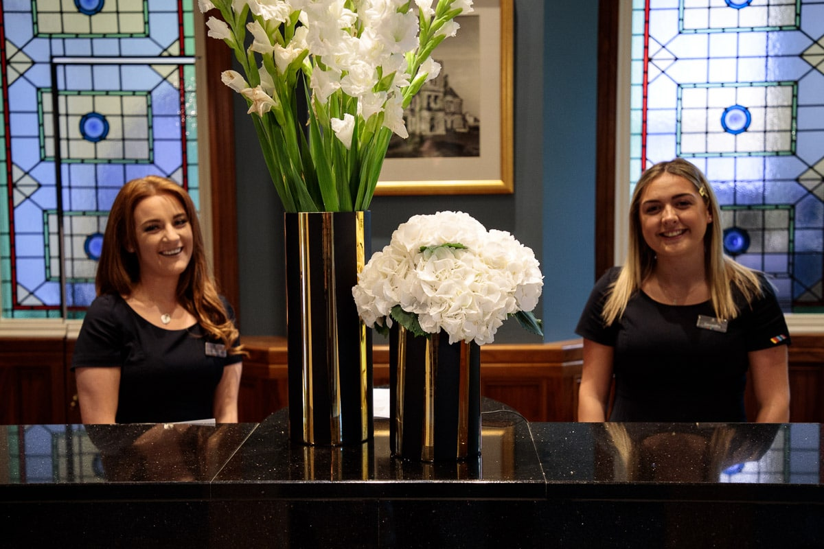 Photo of two of Culloden Estate and Spa's front desk personnel.