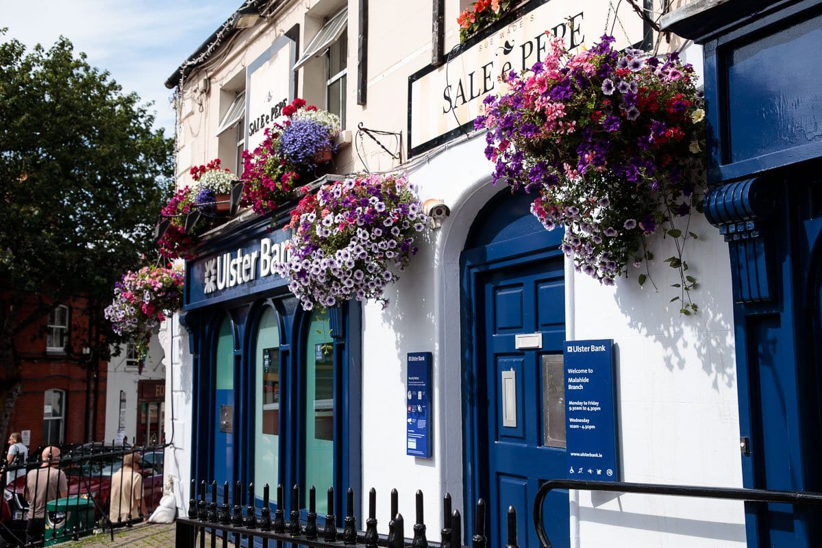 A photo of buildings in downtown Malahide festooned with flowers.