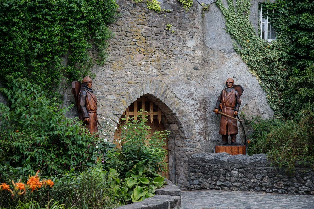 Photo of one of the entrances of Malahide Castle guarded by two carved wood knights.