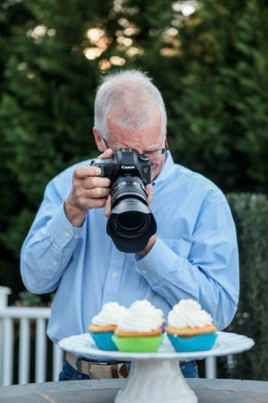 Photo of Scott photographing a plate of cupcakes with a Canon 6D camera.