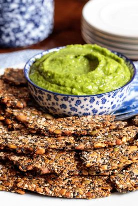 Vertical picture of seeded crackers and avocado dip