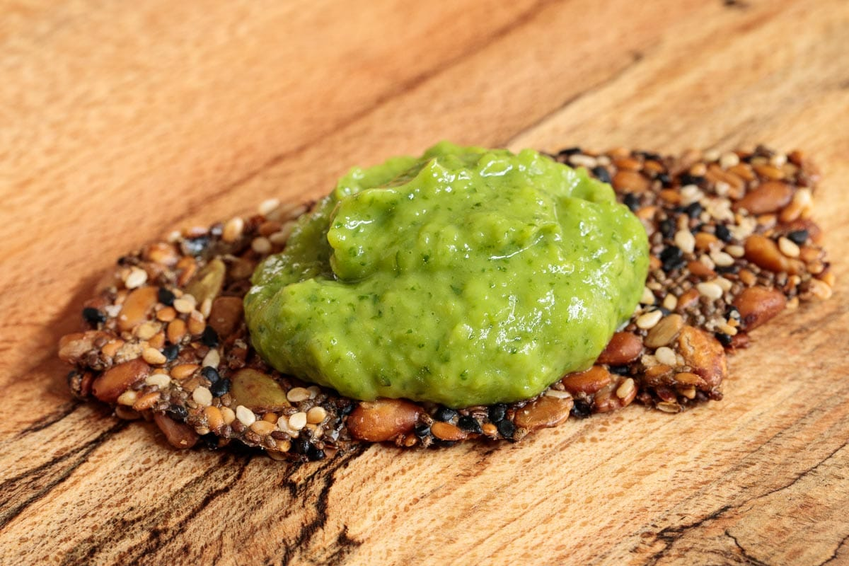 Closeup photo of a Easy Pine Nut Seeded Cracker on a wood appetizer board with a spoonful of Guasacaca dip on top.