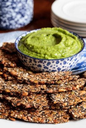Vertical photo of a batch of Pine Nut Seeded Crackers on an appetizer plate with a dish of avocado dip.