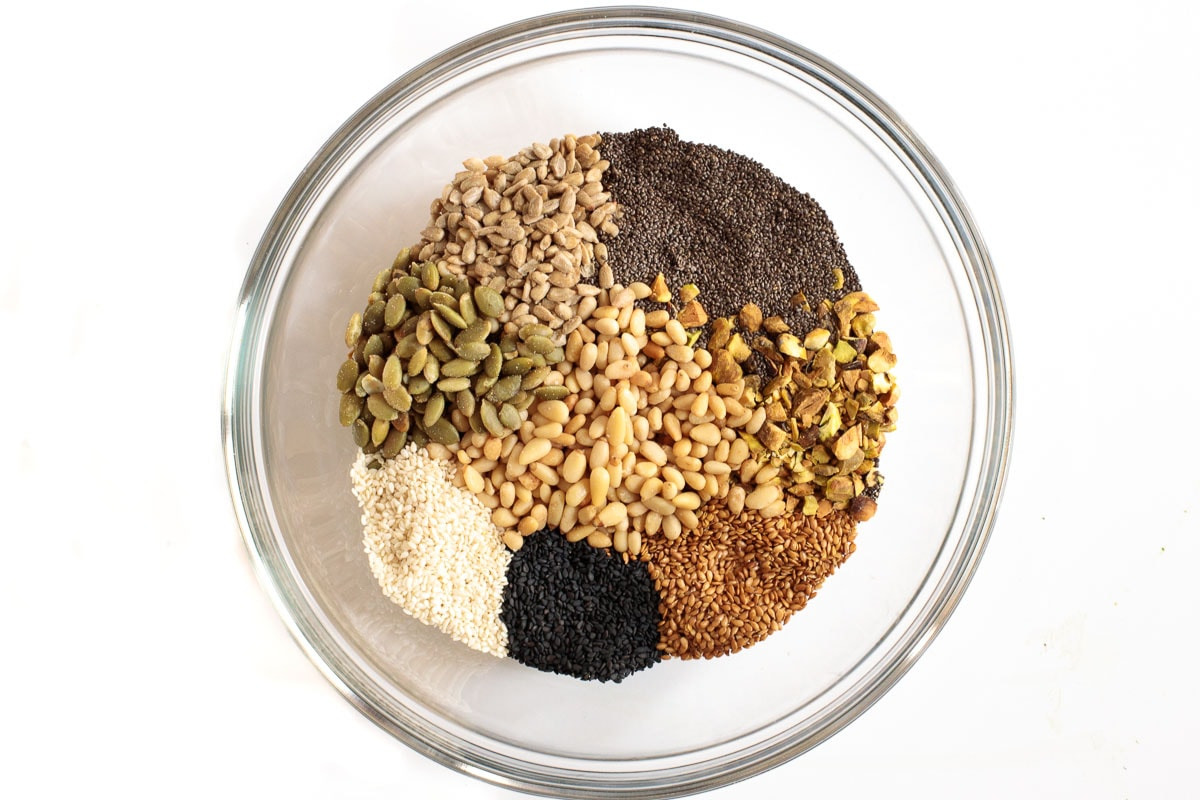 Overhead photo of a bowl containing all the individual ingredients for making Easy Pine Nut Seeded Crackers.