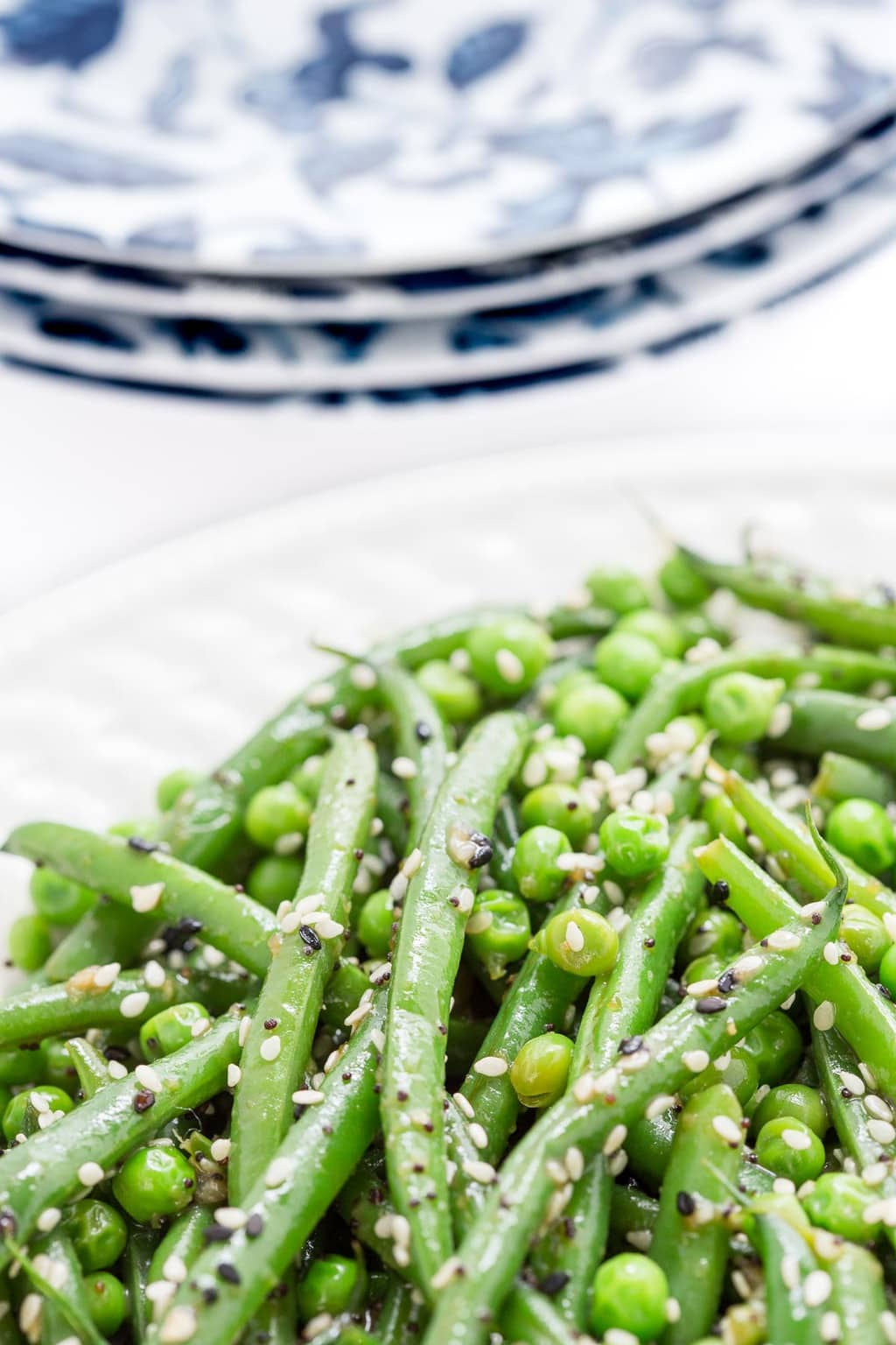 Vertical extreme closeup photo of Sesame Ginger Green Bean Salad on a white serving plate.