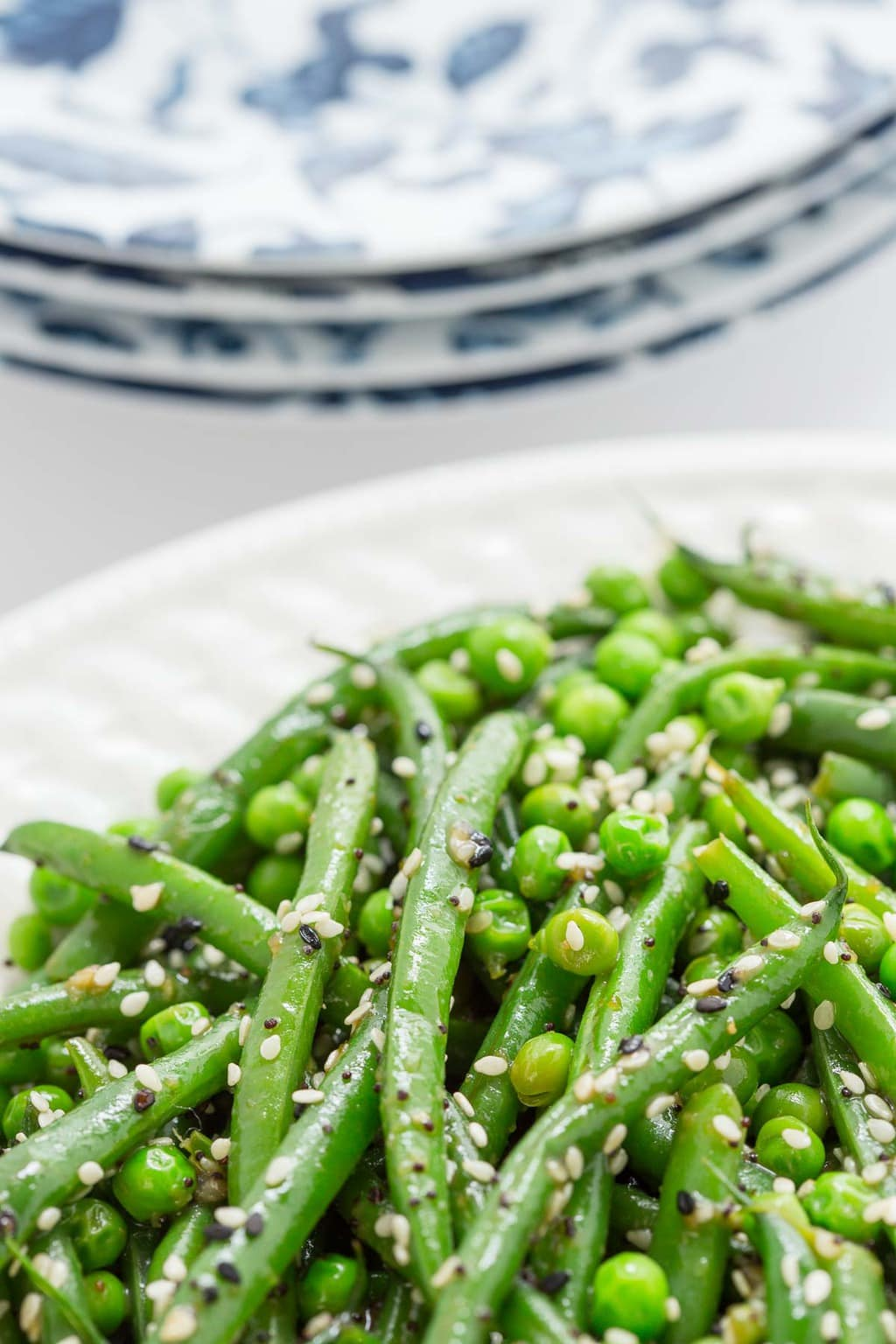 Side photo of a white serving platter filled with Sesame Ginger Green Bean Salad. Individual blue and white patterned serving plates are in the background.