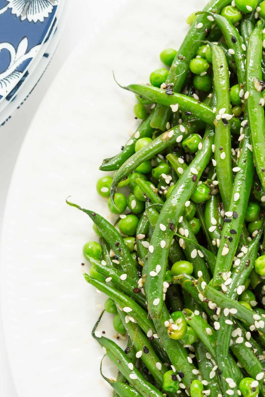Overhead side photo of a white serving plate filled with Sesame Ginger Green Bean Salad.