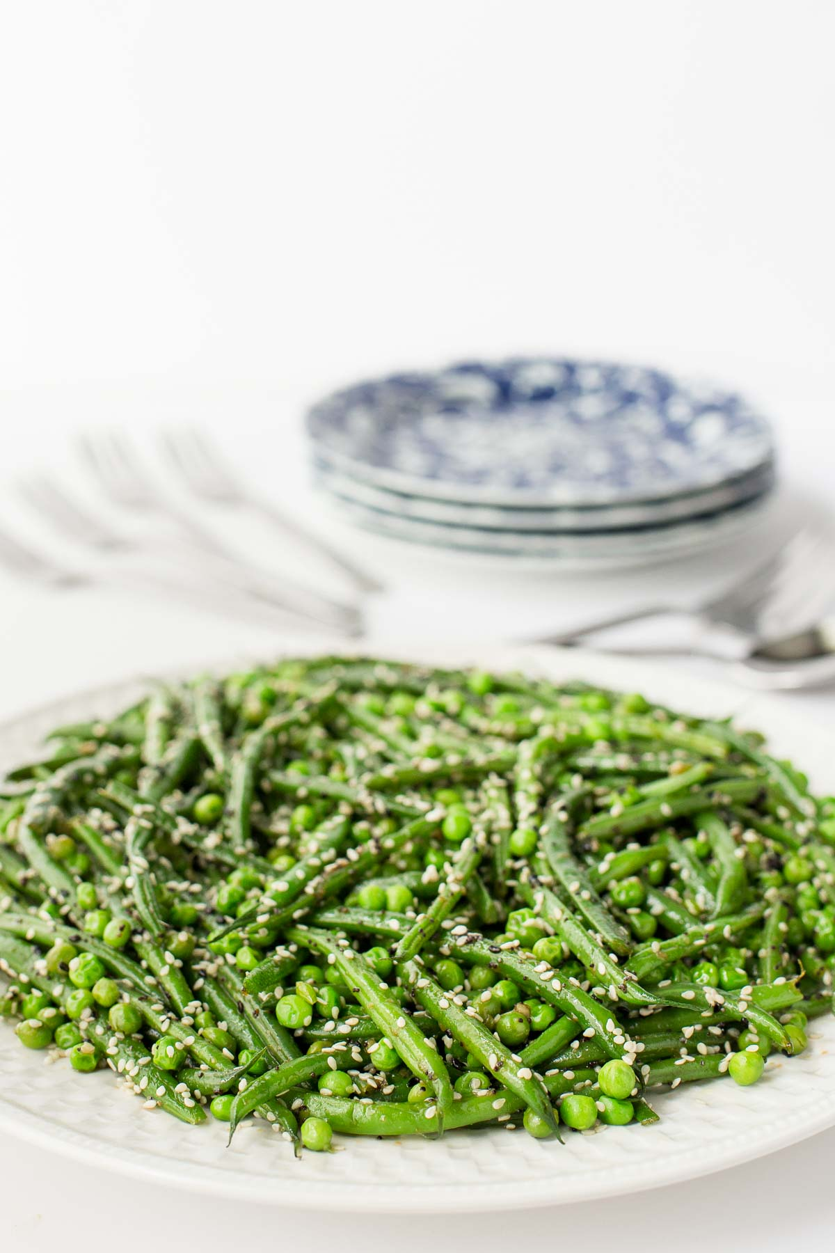 Photo of a white serving platter of Sesame Ginger Green Bean Salad with table settings in the background.