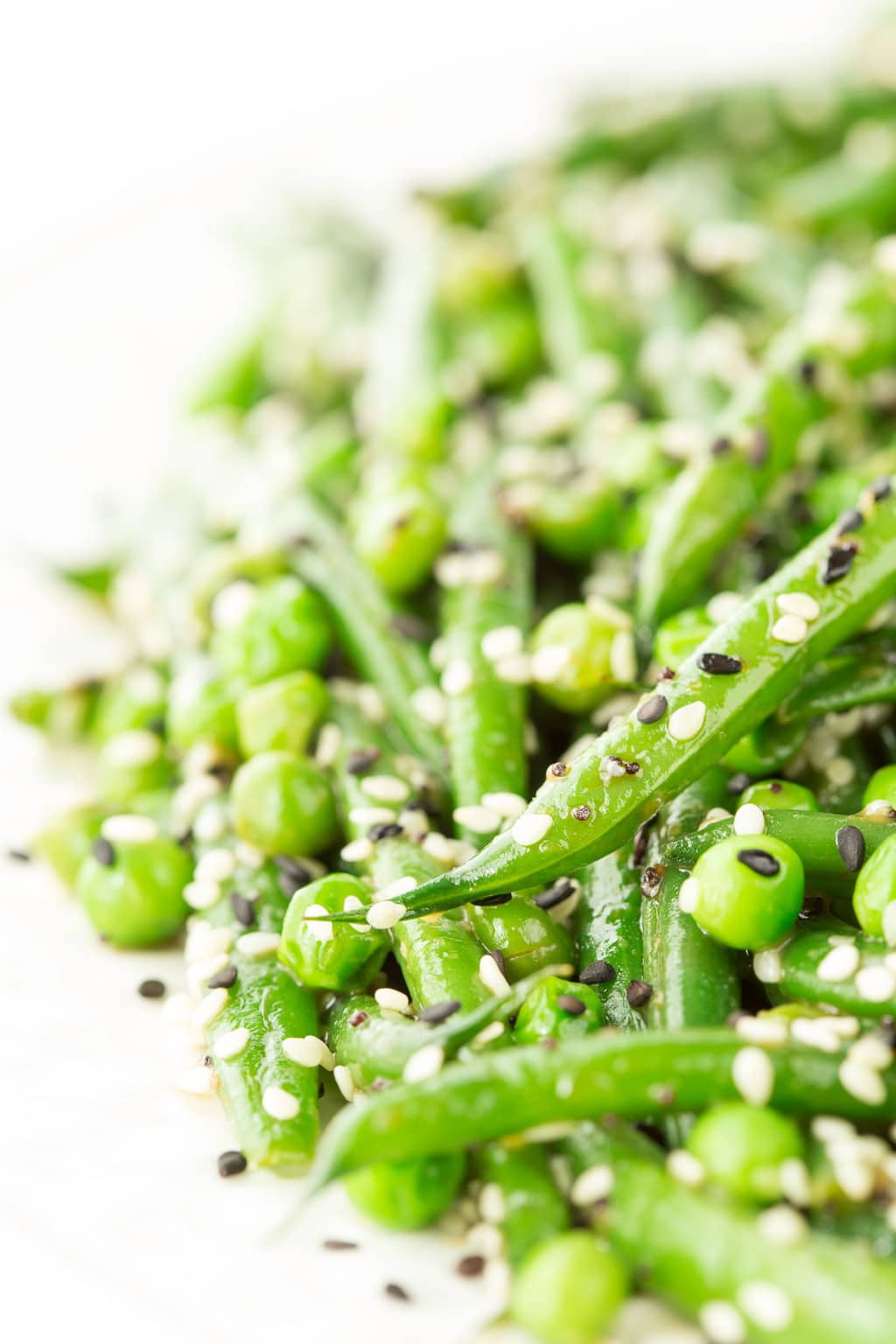 Vertical extreme closeup photo of Sesame Ginger Green Bean Salad on a white serving platter.