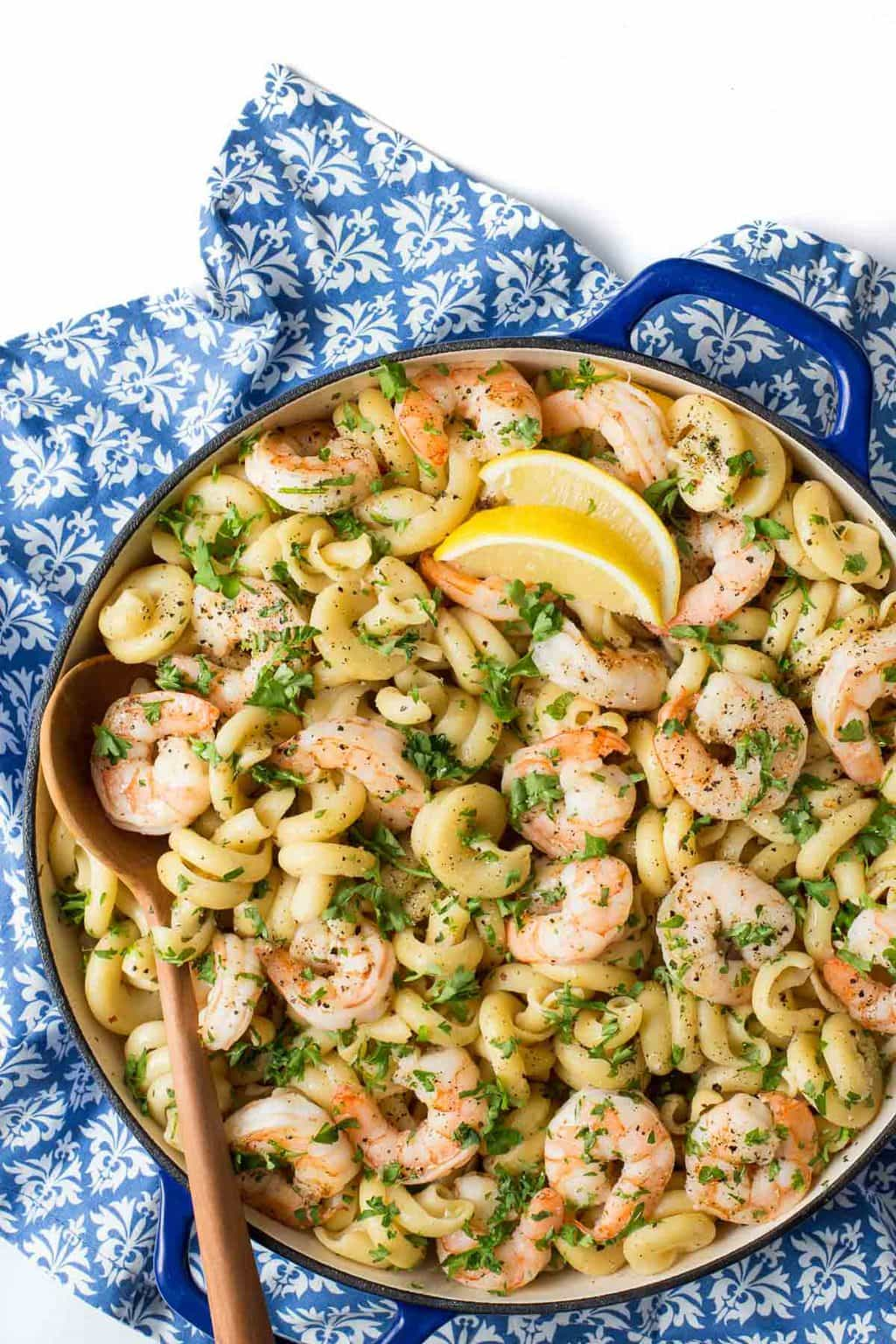 Overhead photo of a blue skillet filled with Skillet Pasta Shrimp Scampi on a blue and white patterned napkin.