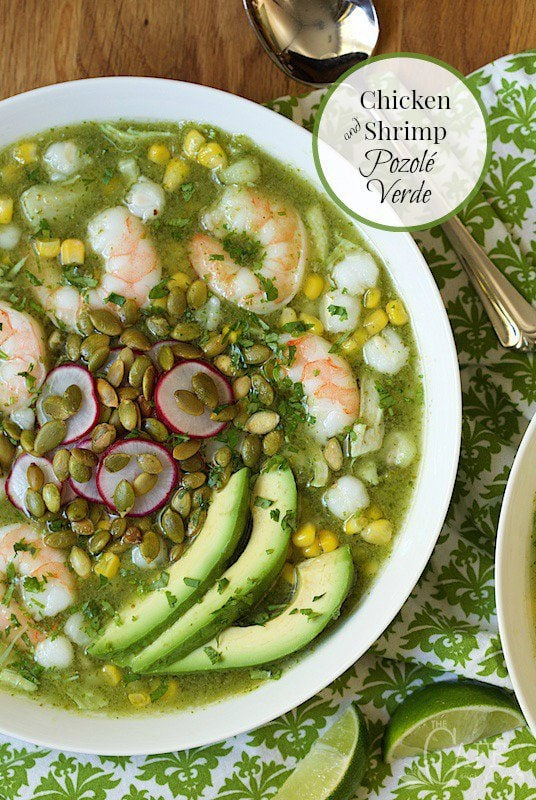 Overhead photo of a bowl of Shrimp and Chicken Pozolé Verde on a wood table with green and white patterned napkins underneath. A title graphic in a circle is at the top right corner.