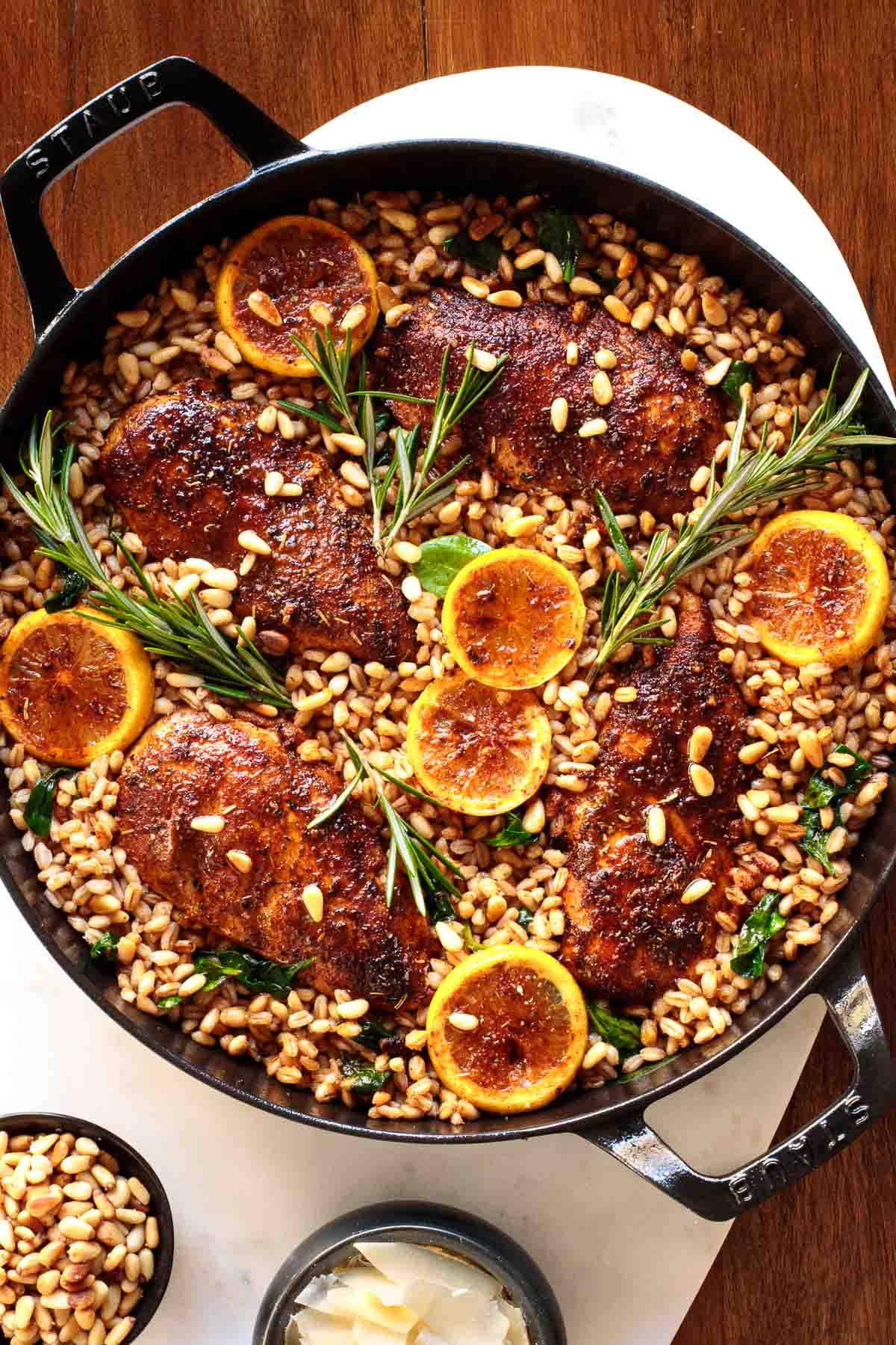 Photo of a cast iron brasier pan of Skillet Lemon Rosemary Chicken and Farro.